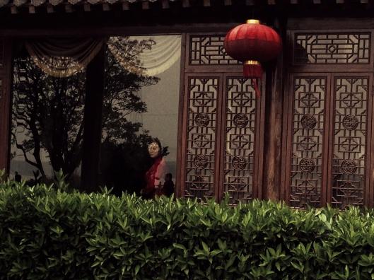 Mulher observa da janela de um restaurante tradicional em Wuhu (Foto: Priscila Dal Poggetto)